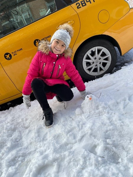 girl in pink coat with small snowman in front of a taxi