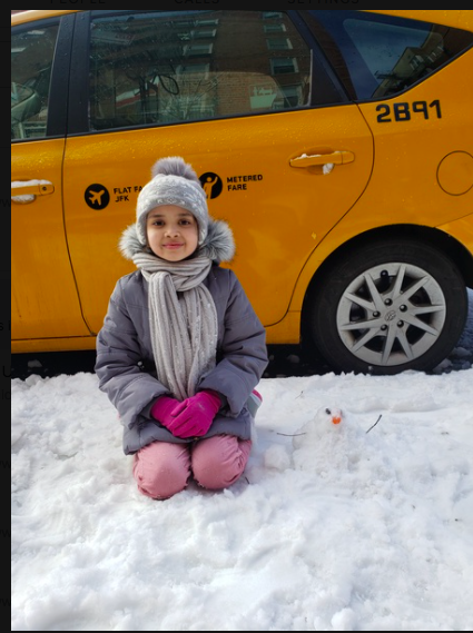 girl sitting in front of a taxi and her very small snowman