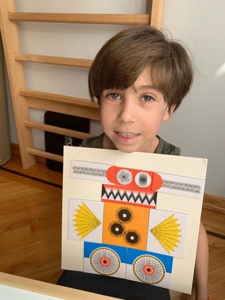 boy holds the orange monster he made