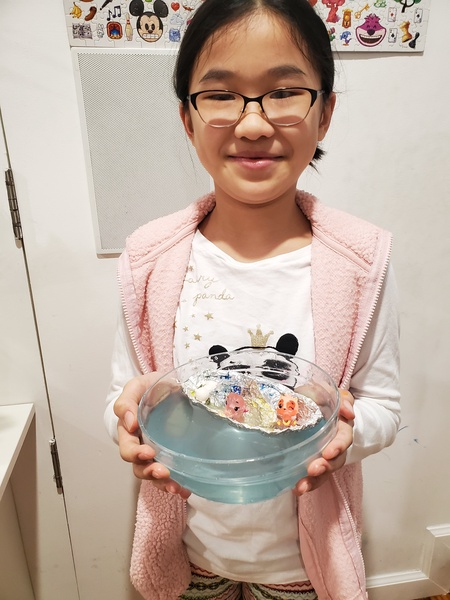 girl holds a bowl of water with a boat