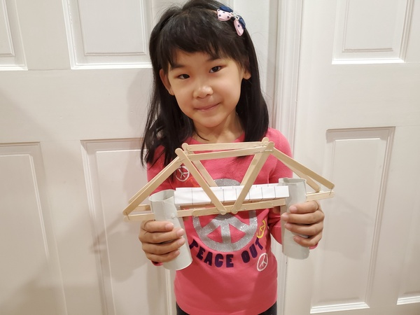 the girl holds the bridge she made with paper and popsicle sticks