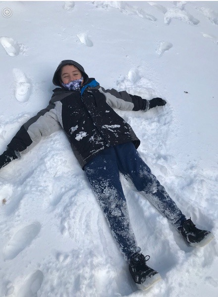 boy laying in the snow building a snow angel