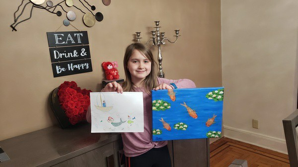 girl holds writing and artwork on canvas