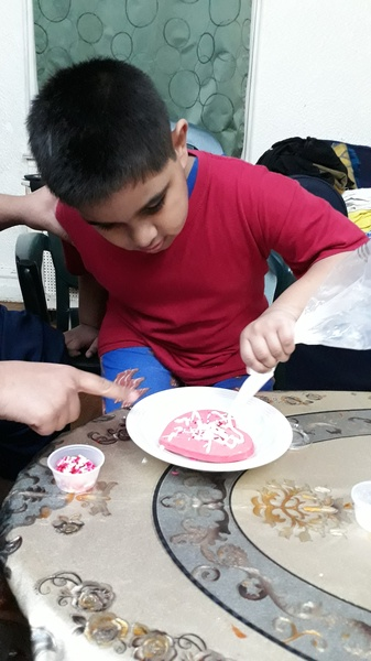 child uses icing to decorate his heart cookie