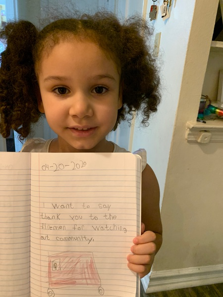 child holds her notebook to share her work