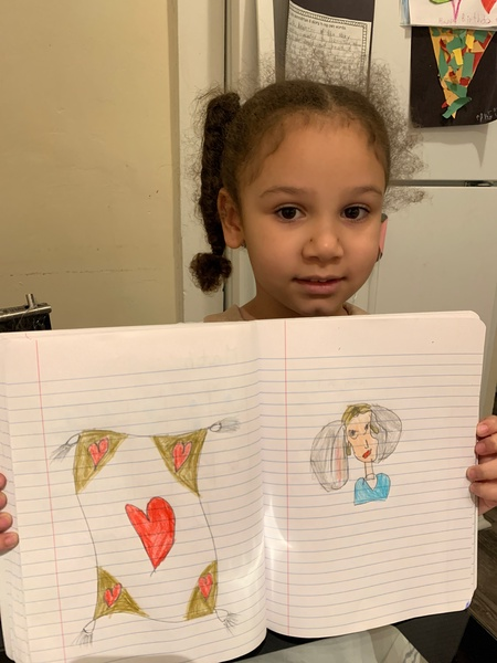 girl holds her notebook to share her work