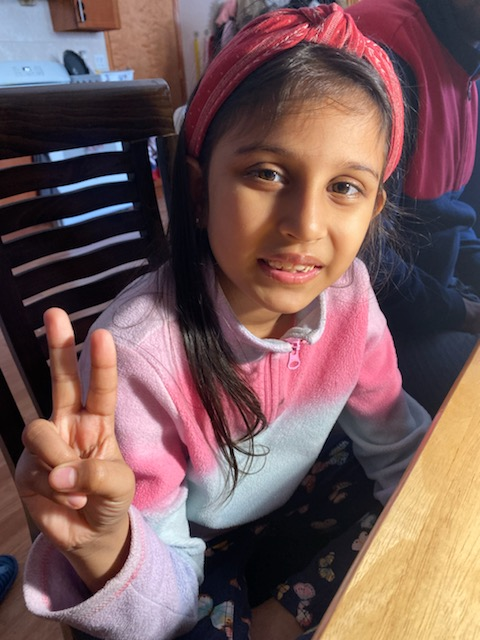 girl gives peace sign at the table