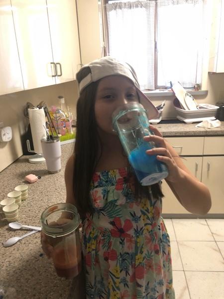 child drinks a blue liquid
