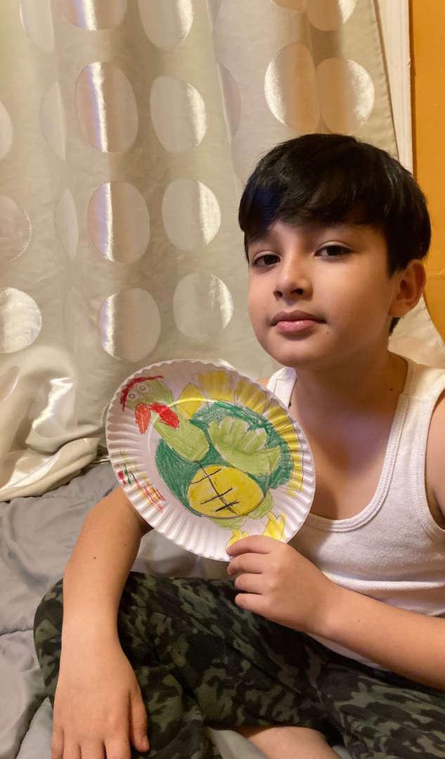 Boy holding a turkey drawn on a plate