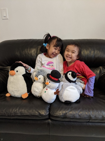 children sit on the couch with their stuffed winter animals