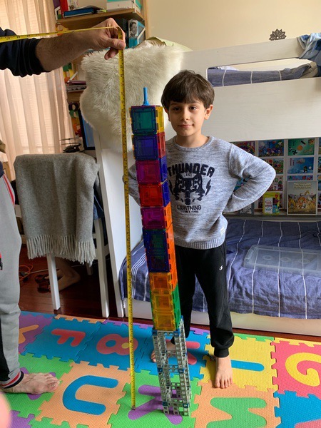 child stands near the structure that is almost as tall as him