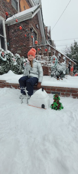 girl sitting next to her snow house