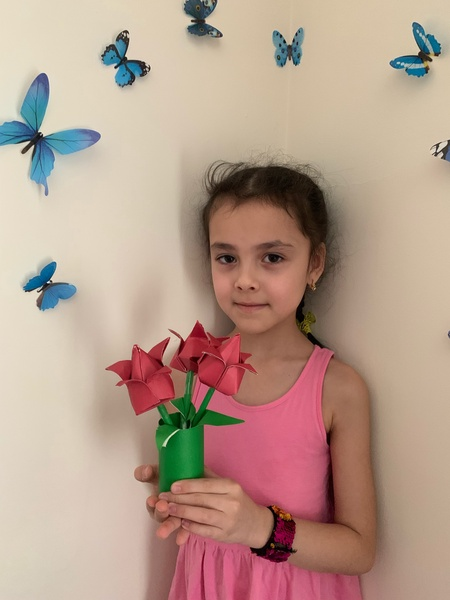 child holds the vase and flowers she made