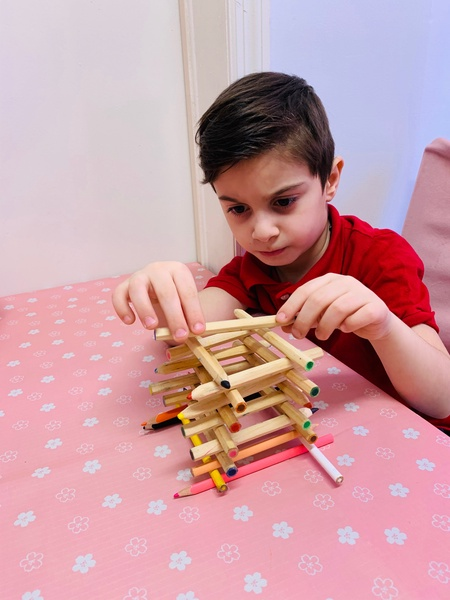 child works to carefully place the sticks on his building