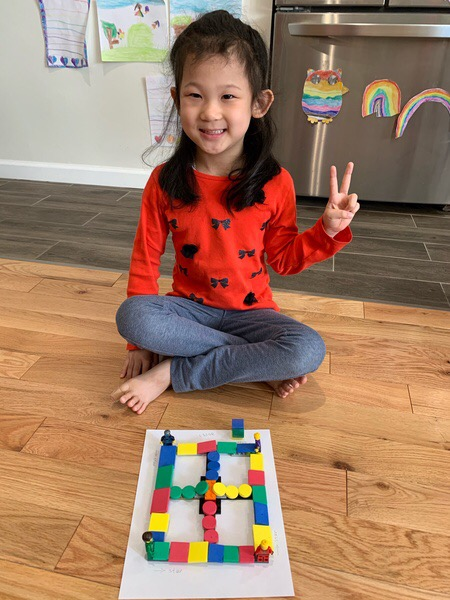 girl gives a piece sign behind her maze