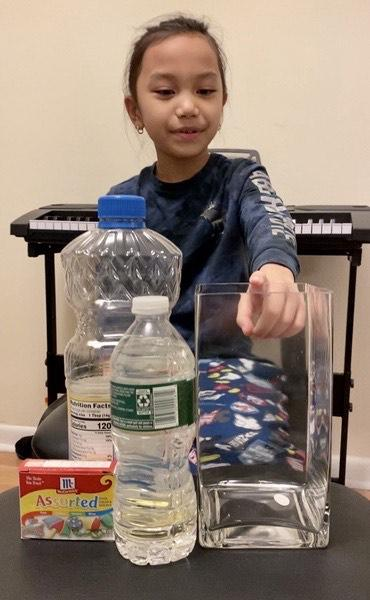 the child points to the container next to the oil and water bottles