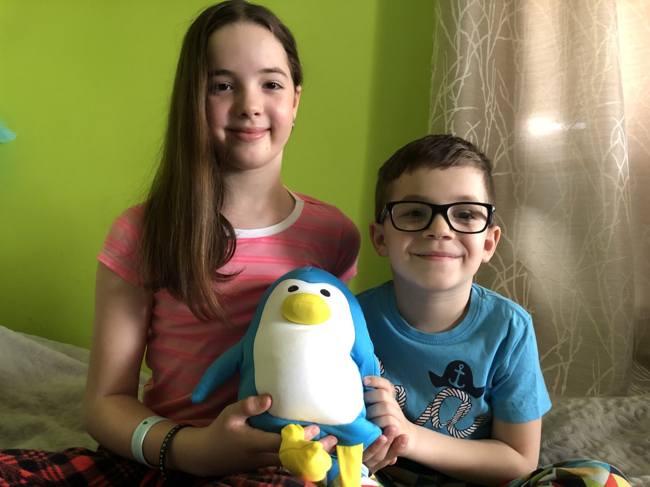 siblings pose with a penguin