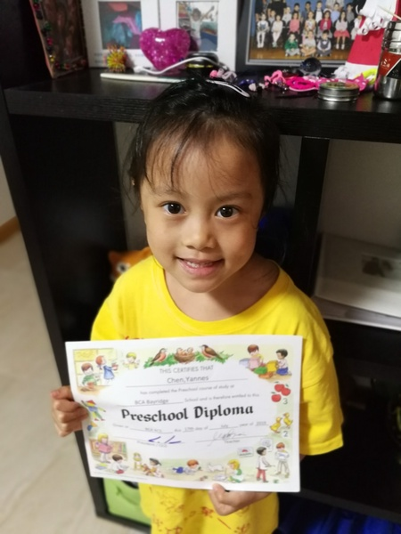 child holds up her certificate for a picture