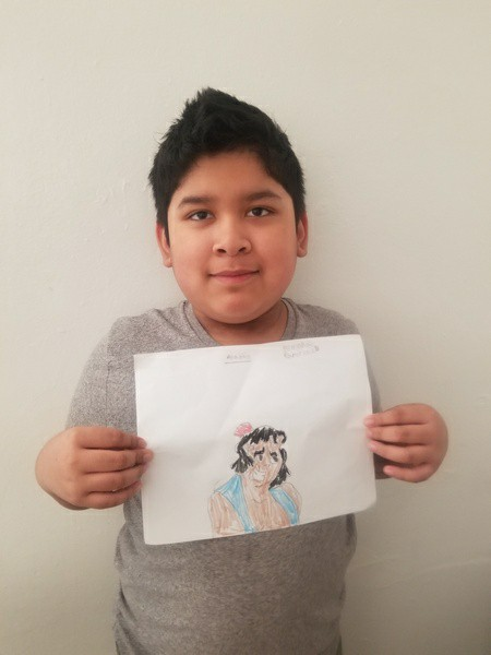 boy holds a picture of Aladdin