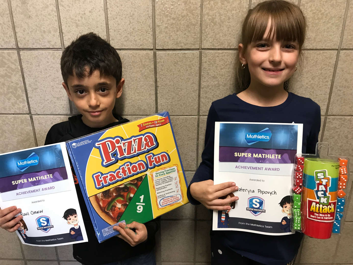 Two students hold games and certificates.