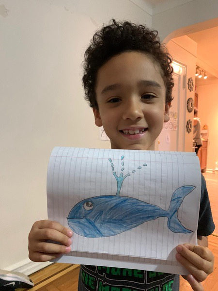 child shares his whale drawing
