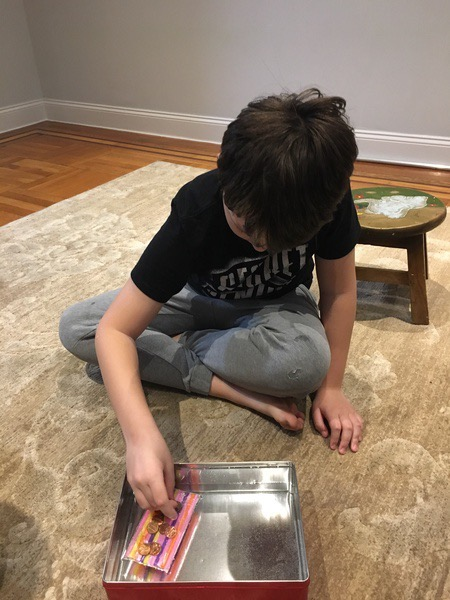 the child sits on the floor placing the pennies in the boat