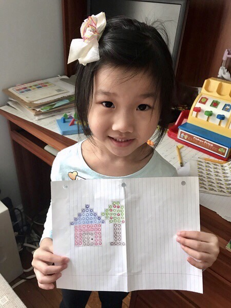 Girl happily shares Lego drawing