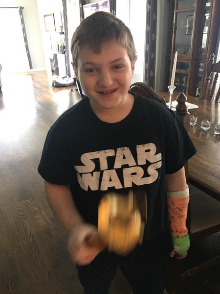 the boy in the Star Wars shirt smiles