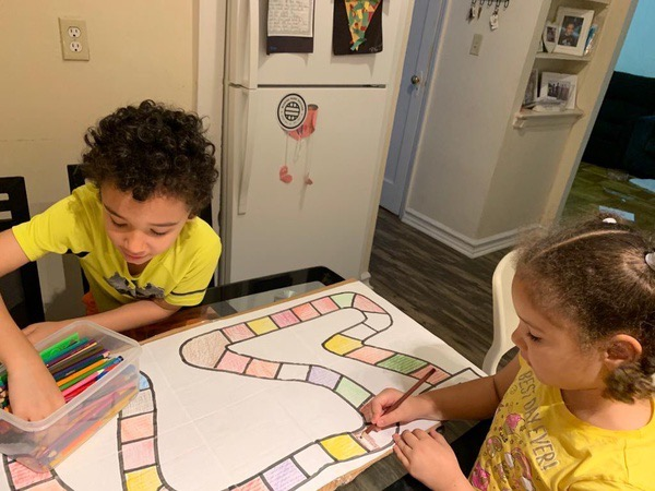 two children in yellow work together to make a board game