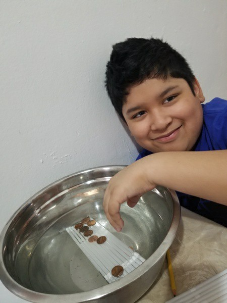 child smiles as her sits next to the bowl with his penny boat