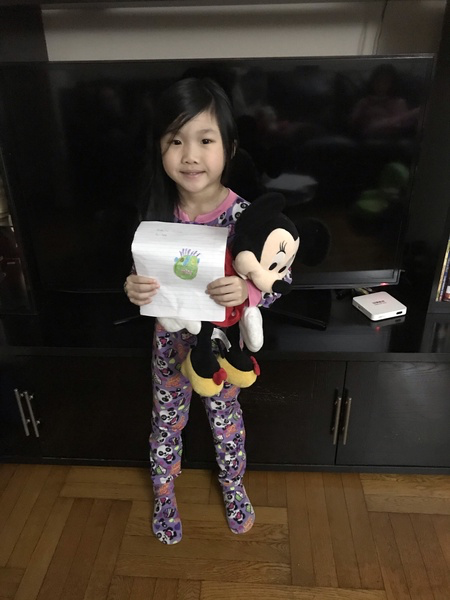 child holds her monster drawing while having Minnie Mouse in her hand