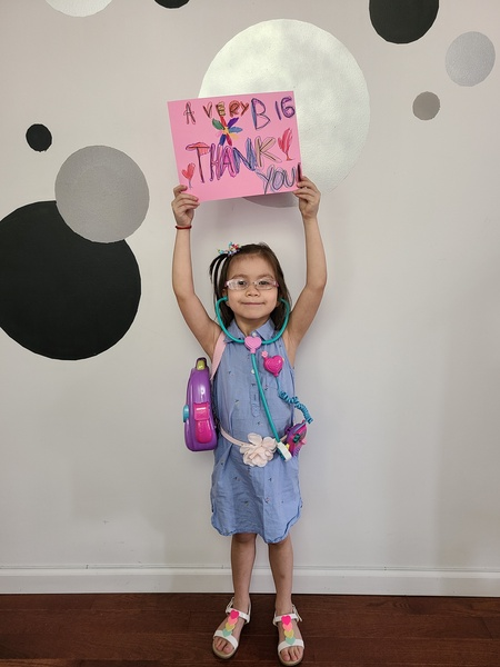 student holds a pink paper above her head