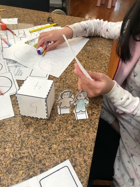 child uses paper to make pieces for her board game