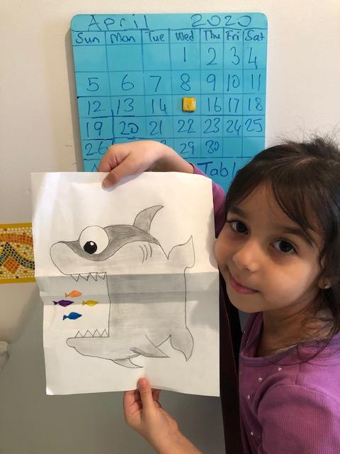 Girl shows artwork of a shark eating fish