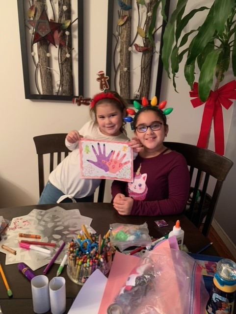 Two girls holding pink and purple hands project