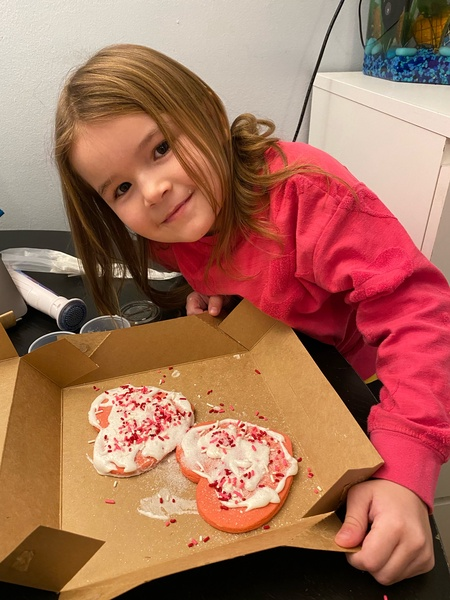 girl in pink smiling with her cookies