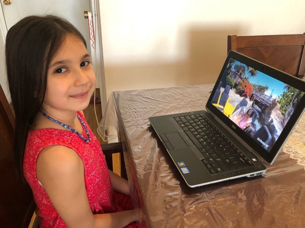 child smiles while working on the computer