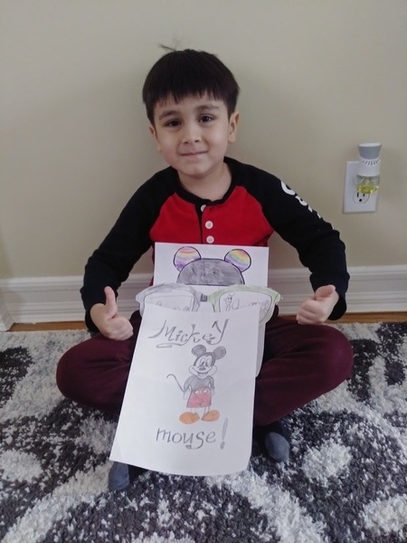 boy giving thumbs up with his drawing of Mickey Mouse