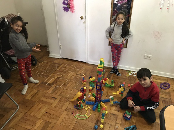 three children stand around the colorful structure they made