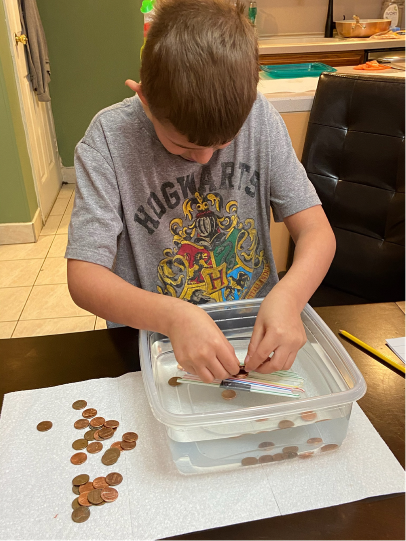 the child in a gray shirt puts the pennies on the boat