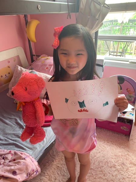 child standing holding drawing and pink stuffed animal in her bedroom