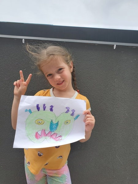 child holds drawing while giving the peace sign