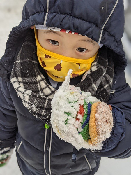 boy in a mask playing in the snow