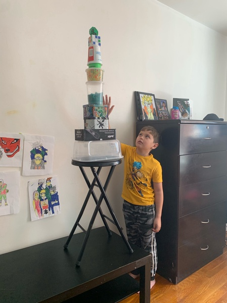 the boy cannot reach the top of his creation