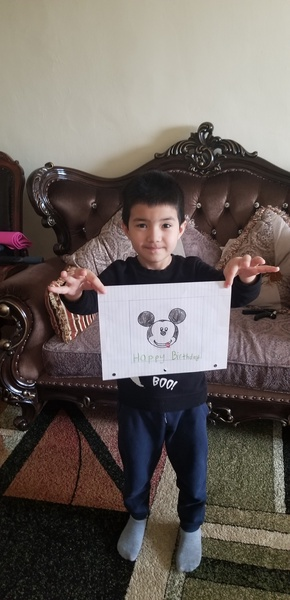 boy holding his mickey drawing