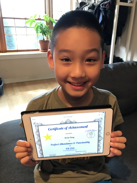 Smiling 3rd grader holds his certificate