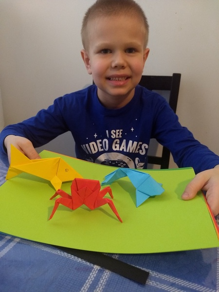 Happy student showing origami sea creatures he made