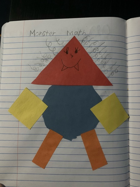 child made a monster picture using construction paper and shapes