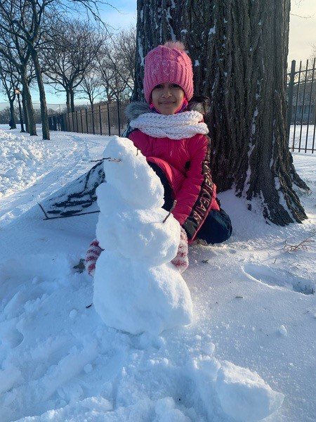 child standing next to a snowman almost as tall as her
