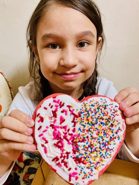 student shows her heart shaped cookie decorated with red and pink sprinkles